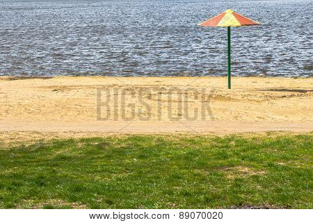 beach umbrella standing alone on the lake