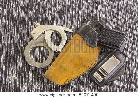 firearm lying on the table, metal police handcuffs