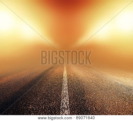 empty asphalt road in heavy fog at night