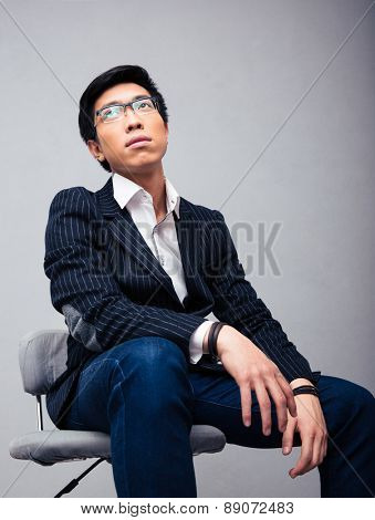 Pensive young businessman sitting on the chair over gray background and looking up