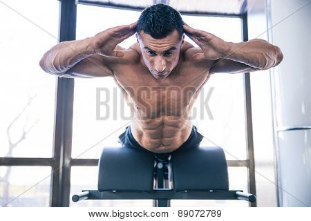 Handsome muscular man flexing back muscles on bench in gym