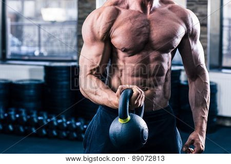 CLoseup image of a man doicing exercise with kette ball in gym