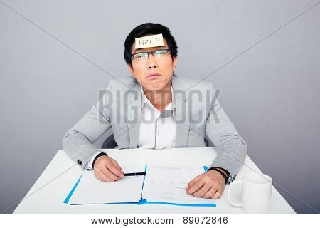Tired asian businessman sitting at the table with adhesive note over gray background