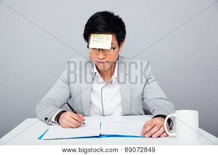Businessman sitting at the table and writing something in document with adhesive note
