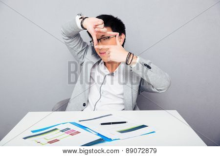 Asian young businessman sitting at the table and making frame with fingers over gray background. Looking at camera through fingers