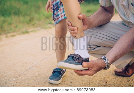 Grandfather putting shoe to his grandson outdoors