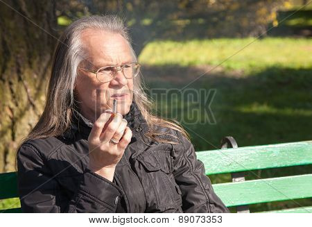 Elderly Gray-haired Man In Glasses Smoking A Cigarette