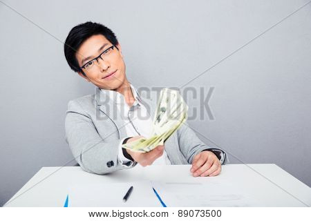 Happy asian businessman sitting at the table and holding money bills over gray background. Looking at camera