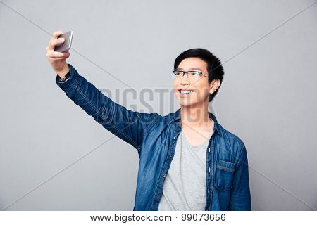 Smiling young asian man making selfie photo on smartphone over gray background