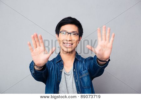 Happy asian man in glasses making stop gesture with palm over gray background