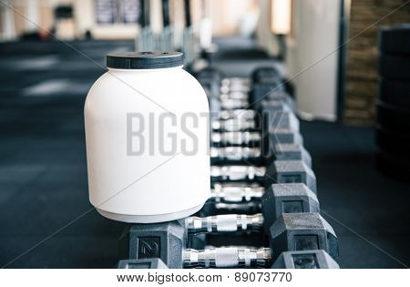 Closeup image of a plastic container with sports nutrition on dumbbells in gym