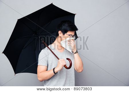 Sick asian man holding umbrella and blowing nose over gray background