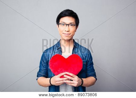 Asian man holding red heart over gray background and looking at camera