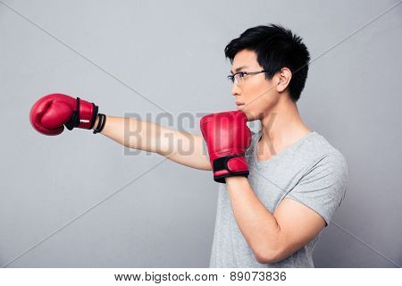 Asian man fighting in boxing gloves over gray background