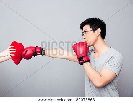 Concept image of a man in boxing gloves hitting at heart over gray background