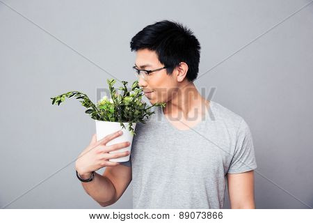 Asian man smelling flowers in a pot over gray background