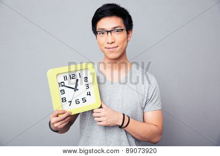 Happy asian man holding big clock over gray background and looking at camera