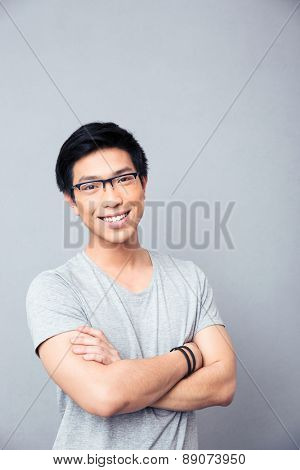 Portrait of a happy asian man in glasses standing with arms folded over gray background. Looking at camera
