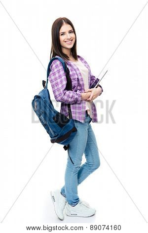 Full length portrait of a smiling young woman standing with backpack and tablet computer. Looking at camera