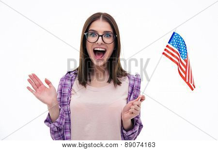 Surprised young woman with glasses holding US flag and screaming over white background. Looking at camera