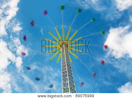 Attraction Carousel on chains against a blue sky with clouds