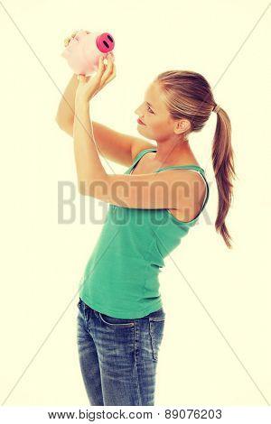 Young blonde woman holding piggybank