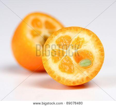 Halved kumquat on white background