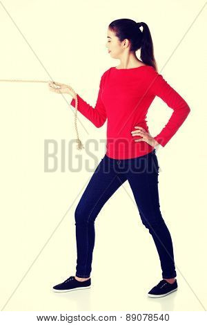 Young attractive woman pulling a rope