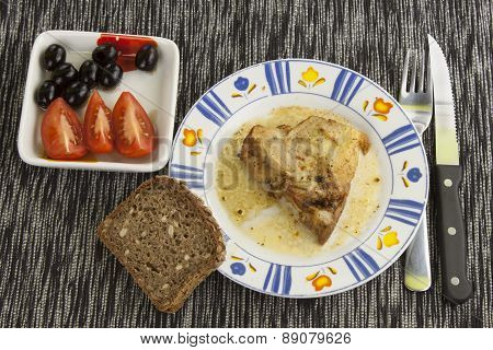 roast pork and bread with olives and tomatoes