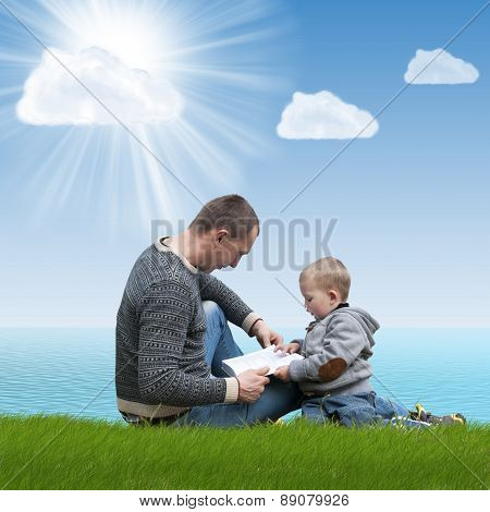 dad and son reading a book on nature