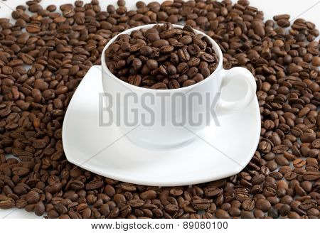Coffee beans in a cup on the table and on a white background.