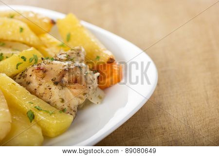 Roasted Chicken With Potatoes And Herbs On White Plate