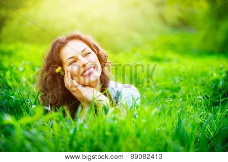 Beautiful Young Woman Outdoors. Enjoy Nature. Healthy Smiling Girl lying in Green Grass