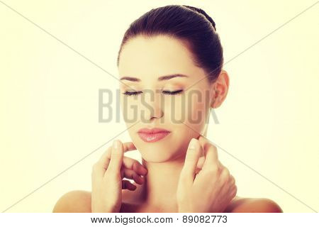 Portrait of a beautiful woman touching her neck