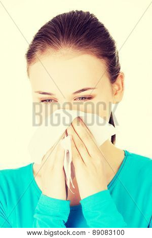 Young beautiful blonde woman sneezing