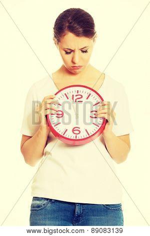 Woman holding a big clock
