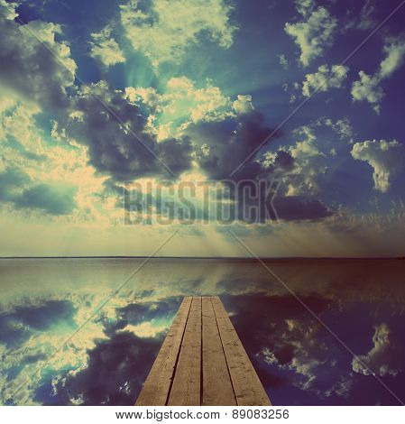 beautiful landscape with wooden pier on big lake and sky reflection - vintage retro style