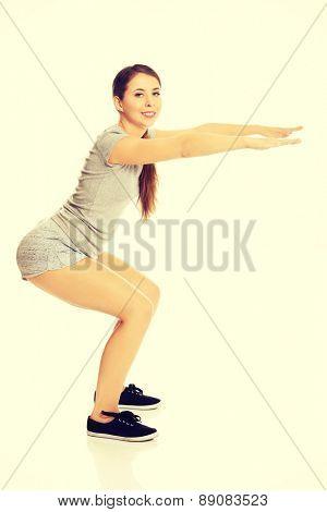 Young active woman doing squats