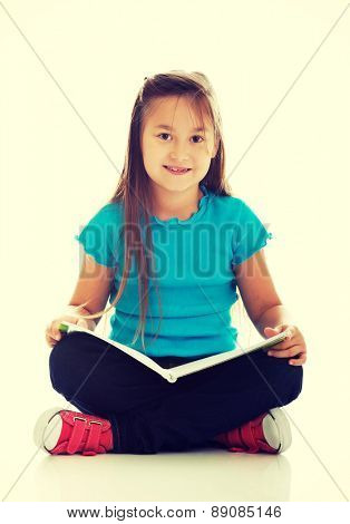 Cute little girl sitting cross legged and learning