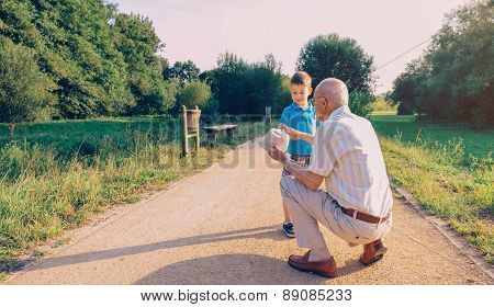 Grandfather showing his hat to grandchild outdoors
