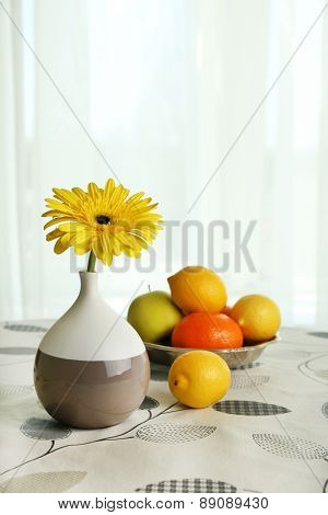Color gerbera flower in vase and fruits on table on curtains background