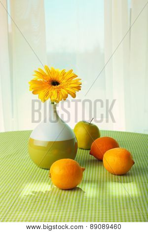 Color gerbera with fruits on table on curtains background