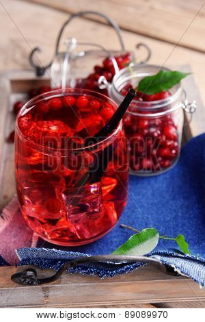Compote with red currant on wooden tray, closeup
