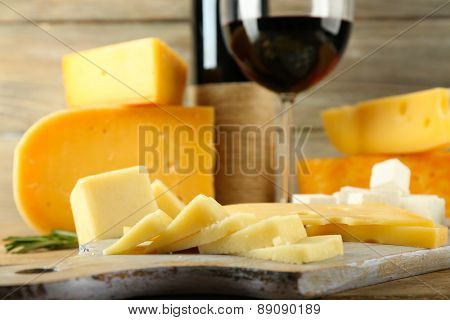 Various types of cheese with wine on table close up