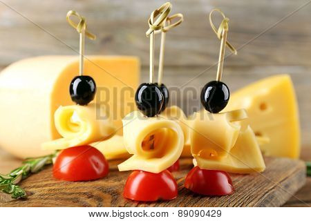 Cheese canapes with cherry tomatoes and olives on wooden background