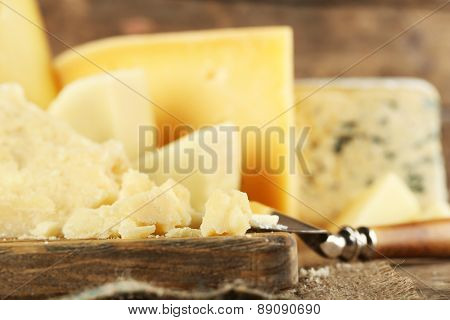 Different sort of cheese on wooden cutting board, closeup