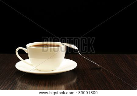 Cup of coffee on wooden table, on dark background