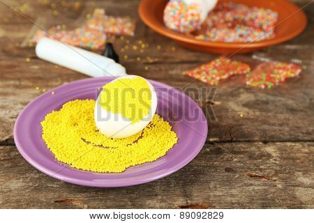 Decorating Easter egg on color plate on wooden table, closeup
