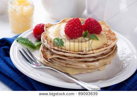 Stack of pancakes with lime curd and raspberries