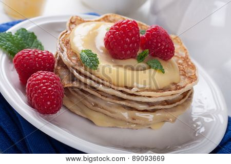 Delicious pancakes with lime curd and raspberries.
